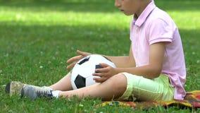 Ensamt pojkesammanträde parkerar in med bollen, inga vänner för att spela med, pennalismproblemet arkivfilmer