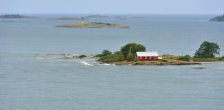 Ensamt rött hus på stenig kust av Östersjön Royaltyfri Foto