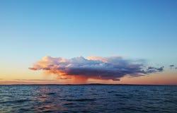 Ensamt regnmoln mot den klara himlen på solnedgången Arkivbilder