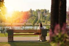 Ensamt sammanträde för ung kvinna på en bänk i parkera nära sjön på solnedgång arkivbilder