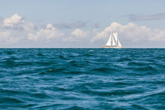 Ensamt segla fartyget på horisont på tropiskt vatten Royaltyfri Fotografi
