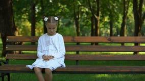 Ensamt sitta för ledsen flicka på väntande på framtida föräldrar för bänk som kommer, föräldralös stock video