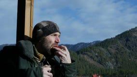 Ensamt skäggigt mananseende på observationsdäcket som ser på ett berg och dricker kaffe eller te från den stora koppen långsamt lager videofilmer