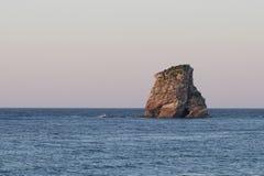 Ensamt vagga ön på solnedgången Hendaye, Frankrike royaltyfri fotografi