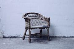 Ensamt vila för gammal stol framme av betongväggen arkivbilder