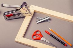 Ensanchador para la lona, el arma de la grapa y otras herramientas en un fondo gris fotos de archivo libres de regalías