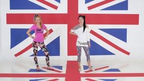 Ensayo de dos ejecutantes femeninos de la danza que se colocan en fondo de la bandera británica almacen de video