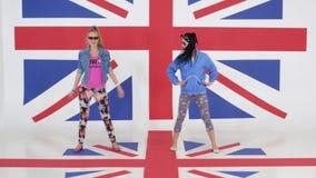 Ensayo de dos muchachas con las gafas de sol que bailan en fondo de la textura BRITÁNICA de la bandera metrajes