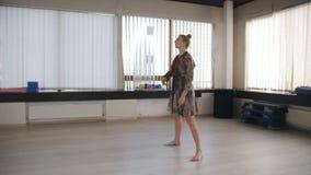 Ensayo de la danza en el pasillo de danza Bailarín de sexo femenino que practica antes del funcionamiento en el cuarto del ensayo almacen de metraje de vídeo