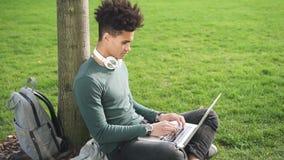 Ensayo que mecanografía del estudiante afroamericano en el ordenador portátil que se sienta en hierba almacen de metraje de vídeo