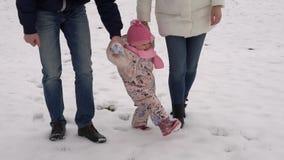 Enseñan la mamá y el papá a caminar mi hija en la nieve Paseo de la familia del invierno almacen de video