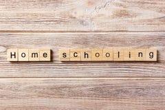 Enseñando en casa la palabra escrita en el bloque de madera Texto que enseña casero en la tabla, concepto foto de archivo