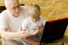 Enseñanza de abuelo cómo trabajar en el ordenador. Foto de archivo libre de regalías
