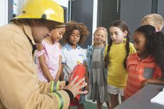 Enseñanza del bombero sobre el extintor a los niños de la escuela en sala de clase imagen de archivo libre de regalías