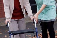 Enseñanza del cuidador usando caminante foto de archivo libre de regalías