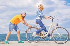 Enseñe al adulto a montar la bici Las ayudas del hombre mantienen el equilibrio y montan la bici Balanza del hallazgo La mujer mo imagenes de archivo