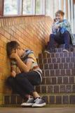 Enseñe al amigo que tiraniza a un muchacho triste en pasillo de la escuela Fotos de archivo libres de regalías