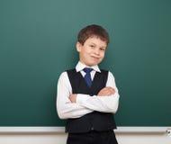 Enseñe al muchacho del estudiante que presenta en la pizarra, hacer muecas y las emociones limpios, vestidos en un traje negro, c Fotografía de archivo libre de regalías