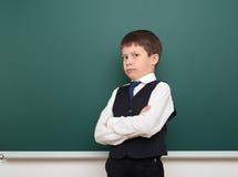 Enseñe al muchacho del estudiante que presenta en la pizarra, hacer muecas y las emociones limpios, vestidos en un traje negro, c Foto de archivo libre de regalías