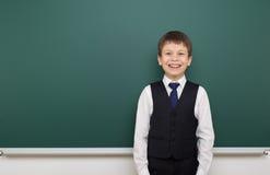 Enseñe al muchacho del estudiante que presenta en la pizarra, hacer muecas y las emociones limpios, vestidos en un traje negro, c Imagen de archivo