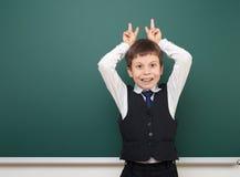 Enseñe al muchacho del estudiante que presenta en la pizarra, hacer muecas y las emociones limpios, vestidos en un traje negro, c Fotos de archivo libres de regalías