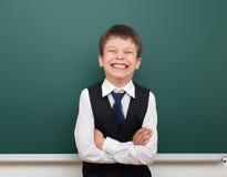 Enseñe al muchacho del estudiante que presenta en la pizarra, hacer muecas y las emociones limpios, vestidos en un traje negro, c Fotos de archivo