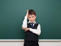 Enseñe al muchacho del estudiante que presenta en la pizarra, hacer muecas y las emociones limpios, vestidos en un traje negro, c Imagen de archivo libre de regalías
