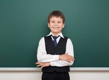 Enseñe al muchacho del estudiante que presenta en la pizarra, hacer muecas y las emociones limpios, vestidos en un traje negro, c Fotografía de archivo