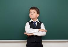 Enseñe al muchacho del estudiante que presenta en la pizarra, hacer muecas y las emociones limpios, vestidos en un traje negro, c Imágenes de archivo libres de regalías