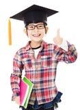 enseñe al niño en casquillo de la graduación con el pulgar para arriba Fotos de archivo