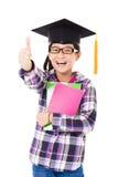 enseñe al niño en casquillo de la graduación con el pulgar para arriba Fotografía de archivo