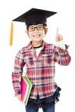 enseñe al niño en casquillo de la graduación con gesto del éxito Fotos de archivo libres de regalías