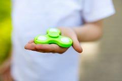 Enseñe al niño que juega con el tri hilandero de la mano de la persona agitada al aire libre Imagen de archivo