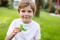 Enseñe al niño que juega con el tri hilandero de la mano de la persona agitada al aire libre Fotos de archivo libres de regalías