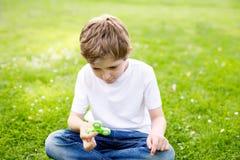 Enseñe al niño que juega con el tri hilandero de la mano de la persona agitada al aire libre Imágenes de archivo libres de regalías