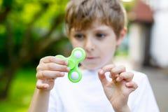 Enseñe al niño que juega con el tri hilandero de la mano de la persona agitada al aire libre Foto de archivo libre de regalías