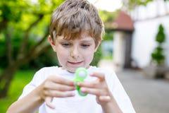 Enseñe al niño que juega con el tri hilandero de la mano de la persona agitada al aire libre Fotografía de archivo libre de regalías