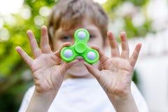 Enseñe al niño que juega con el tri hilandero de la mano de la persona agitada al aire libre Fotos de archivo