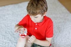 Enseñe al niño que juega con el tri hilandero de la mano de la persona agitada dentro Foto de archivo libre de regalías