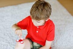 Enseñe al niño que juega con el tri hilandero de la mano de la persona agitada dentro Imagen de archivo libre de regalías