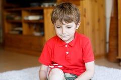 Enseñe al niño que juega con el tri hilandero de la mano de la persona agitada dentro Foto de archivo