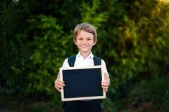 Enseñe al niño que sostiene una pizarra con de nuevo al mensaje de la escuela Imagenes de archivo