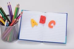 Enseñe el concepto del escritorio con las letras, el libro y los lápices Imágenes de archivo libres de regalías