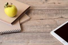 Enseñe el cuaderno, la tableta y la manzana en fondo de madera foto de archivo libre de regalías