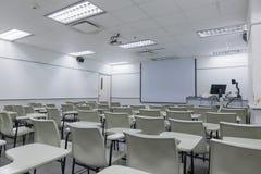 Enseñe el interior de la sala de clase con el fondo del escritorio y del proyector foto de archivo libre de regalías