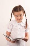 Enseñe el libro de lectura de la muchacha y la mirada de la cámara Imagenes de archivo
