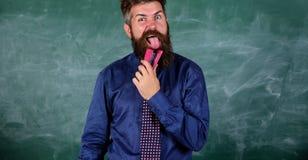 Enseñe el papel Hombre barbudo del profesor con el fondo rosado de la pizarra de la grapadora Prevención de accidentes de la escu imagen de archivo