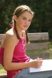 Enseñe la escritura de la muchacha en cuaderno al aire libre Imágenes de archivo libres de regalías