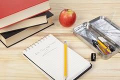 Enseñe la mesa con la libreta, los libros y los sacapuntas de lápiz Imagen de archivo