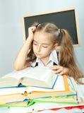 Enseñe a la muchacha que hace la preparación detrás de la pila de libros. Imagen de archivo